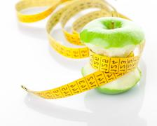 Green apple core and measuring tape - stock photo