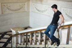 Young man on railing in beautifully decorated building - stock photo