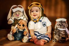 The young airman sitting with his soft toys - stock photo