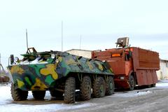Military equipment - an armored troop-carrier and the truck with a machine gu - stock photo