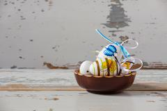 Colorful handmade easter eggs inside a wood bowl Stock Photos