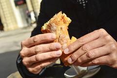 man eating a spanish omelette sandwich - stock photo