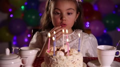 Little girl blowing out the candles of Birthday cake Stock Footage