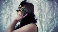 Girl in carnival mask looking to the camera and showing shh sign Stock Footage