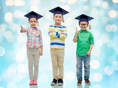 happy children in bachelor hats and eyeglasses - stock photo