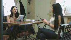 Two girls show each other photos using your tablet Stock Footage