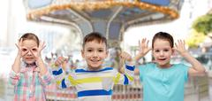Happy little children having fun over carousel Stock Photos