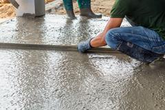 Man mason building a screed coat cement on floor Stock Photos