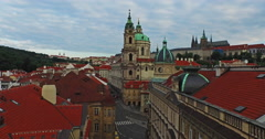 Flying over the old rooftops of Prague from the Charles Bridge, close to Church Stock Footage