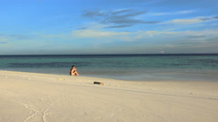 Young woman sit on the beach - Maldives - stock footage