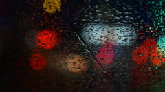 Colorful commuter lights in the rain. Focus on raindrops. Stock Footage