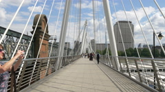 Woman taking pictures and others walking on Golden Jubilee Bridges in London Stock Footage