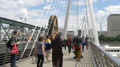 Adults with baby walking on Golden Jubilee Bridges, London Stock Footage