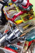 fishing reel on boxes with lures and wobblers - stock photo