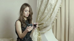 Pretty brunette with a glass of red wine in his hand talking on cell phone. - stock footage