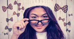 Composite image of smiling asian woman holding eyeglasses - stock photo