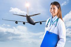 Composite image of asian doctor holding blue binder - stock photo