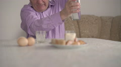 Senior man in blue shirt sits at the table and drinks vodka Stock Footage