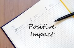 Positive impact write on notebook Stock Photos