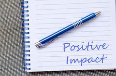 Positive impact write on notebook - stock photo