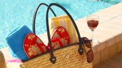 Wine glass, flip flop, straw hat and bag near poolside Stock Footage
