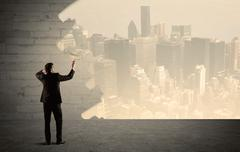 Salesman painting city scape on wall - stock photo