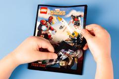 Childs hands open comic book Lego Marvel Super Heroes Stock Photos