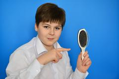 Boy teenager with comb in his hand - stock photo