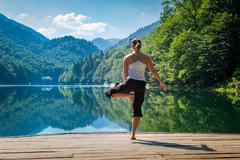 Sport exercises at fresh air in the pier of mountain lake Stock Photos