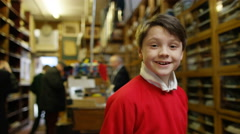 4K Portrait of smiling little boy trying on new school uniform in clothing store Stock Footage