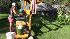 Woman wring child clothes in yard on summer day outdoor. 4K Stock Footage