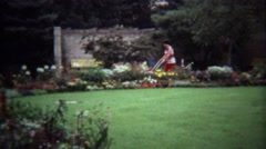 1974: Mother pushing stroller peak flower blossom conservatory. - stock footage