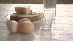 Raw eggs, bacon and bread and vodka on the table - stock footage
