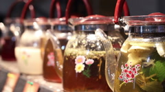 Wide choice of herbal tea drinks in glass teapots standing on cafe counter Stock Footage