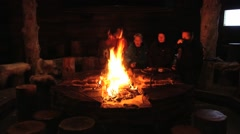 People sit in front of the fireplace in Saariselka, Finland. - stock footage