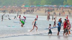 Crowd of people in water on populat balinese tourist attraction Kuta beach Stock Footage