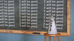 "Classroom with ""I will be good"" written on the chalkboard and a dunce cap - stock footage"