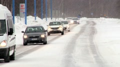 Cars pass by the road covered with ice in the arctic town of Ivalo, Finland. Stock Footage