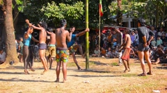 Young men compete to reach a main prize on the top of slick bamboo pole - stock footage