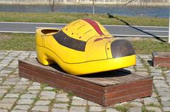 Traditional yellow Dutch wooden shoe on the street Stock Photos