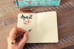 April 25 Calendar Day handwritten on notebook - stock photo