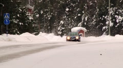 Cars pass by the road covered with ice and snow in Inari, Finland. - stock footage