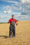Farmer or agronomist inspect in wheat field after harvest - stock photo