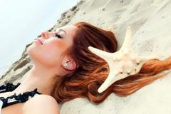 The beautiful girl lies on sea coast with shells nature vacation - stock photo