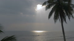 Rays of light shinning through clouds in the sky and reflecting on the ocean Stock Footage