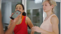 4K Fitness instructor using mobile phone app to train with female clients Stock Footage