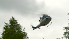 Helicopter flies and lands in the landscape Stock Footage