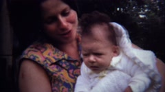 1971: Bright colorful shirt mother rocking newborn baby. Stock Footage