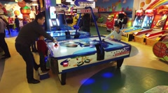 Teenagers playing air hockey game - stock footage