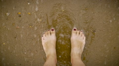 Slow motion of waves gently covering a woman's feet with painted toe nails Stock Footage